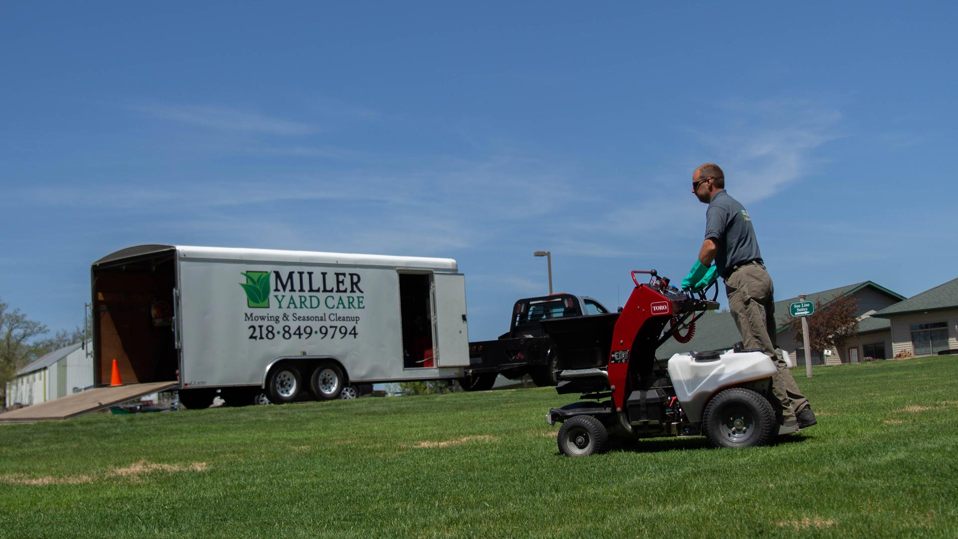 Miller Yard Care & Construction team member applying a fertilization treatment to a lawn in Detroit Lakes, MN.