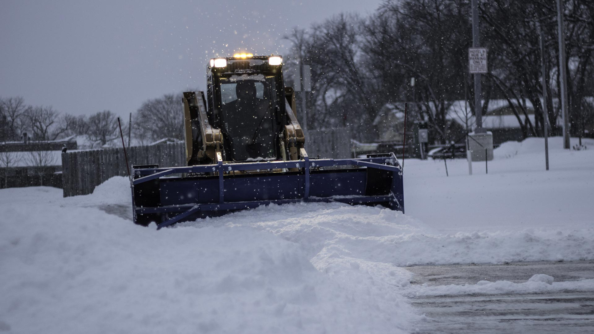 Snow plowing a commercial parking lot and treating with deicer in Detroit Lakes, MN
