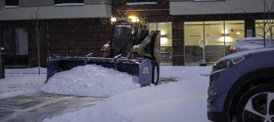 Plowing snow in a hotel parking lot during a cold winter night in Detroit Lakes, MN.