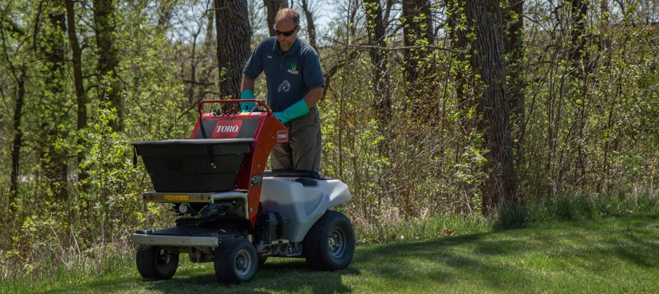 Miller Yard Care & Construction professional treating and fertilizing a lawn in Detroit Lakes, MN.