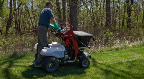 Lawn technician fertilizing a clients lawn in Detroit Lakes, MN.