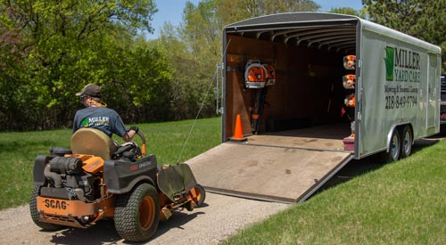 Miller Yard Care & Construction work trailer unloading a mower for a yard cleanup service.